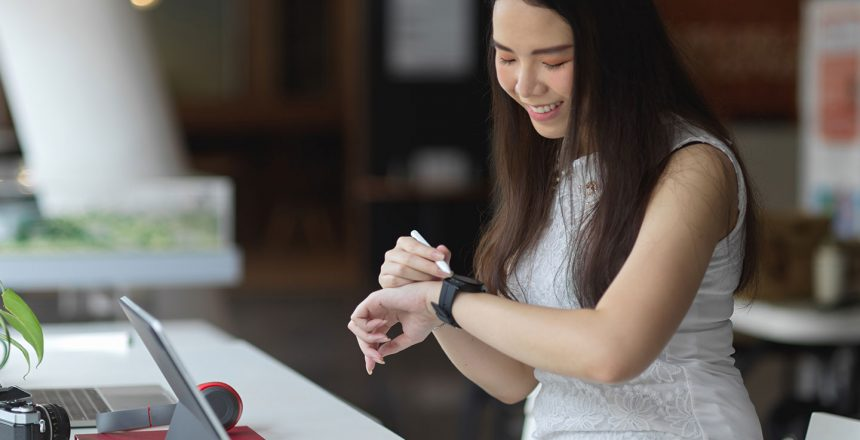 portrait-female-looking-smartwatch-while-working-co-working-space